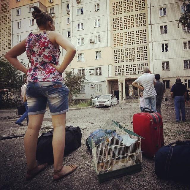 Дончане с тревожными чемоданами смотрят на окна своих частично разрушенных квартир. © Reuters #vestiua #Ukraine #Украина #Don...